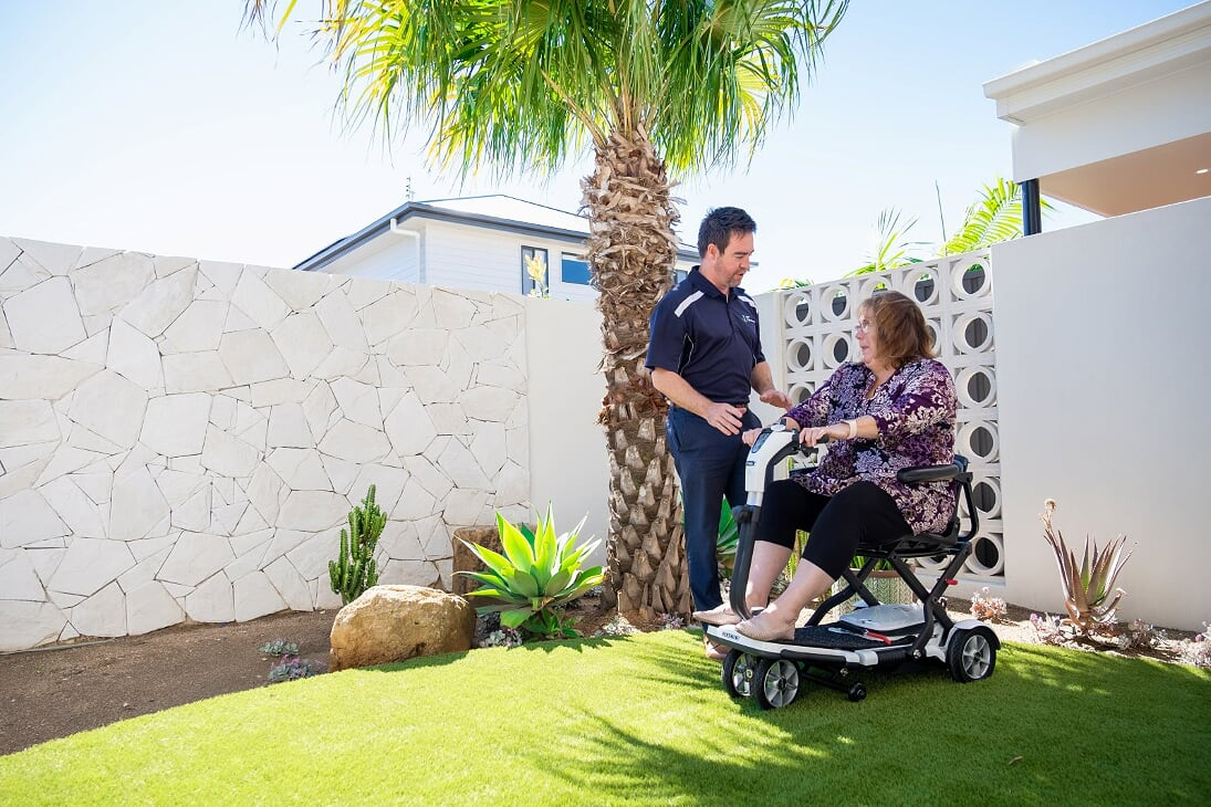 [Male Occupational Therapist Outside With Women Patient Who Is In Her Motorized Scooter]