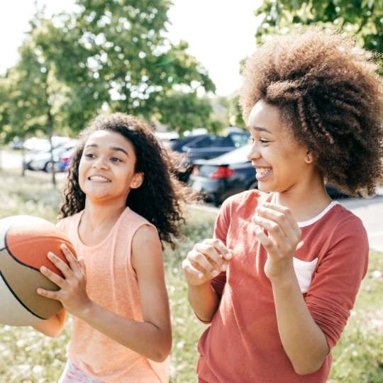 [Two Young Girls In A Park Walking Together And Laughing, One Of The Young Girls Are Holding A Basket Ball, Both Girls Are Wearing Orange Shirts]