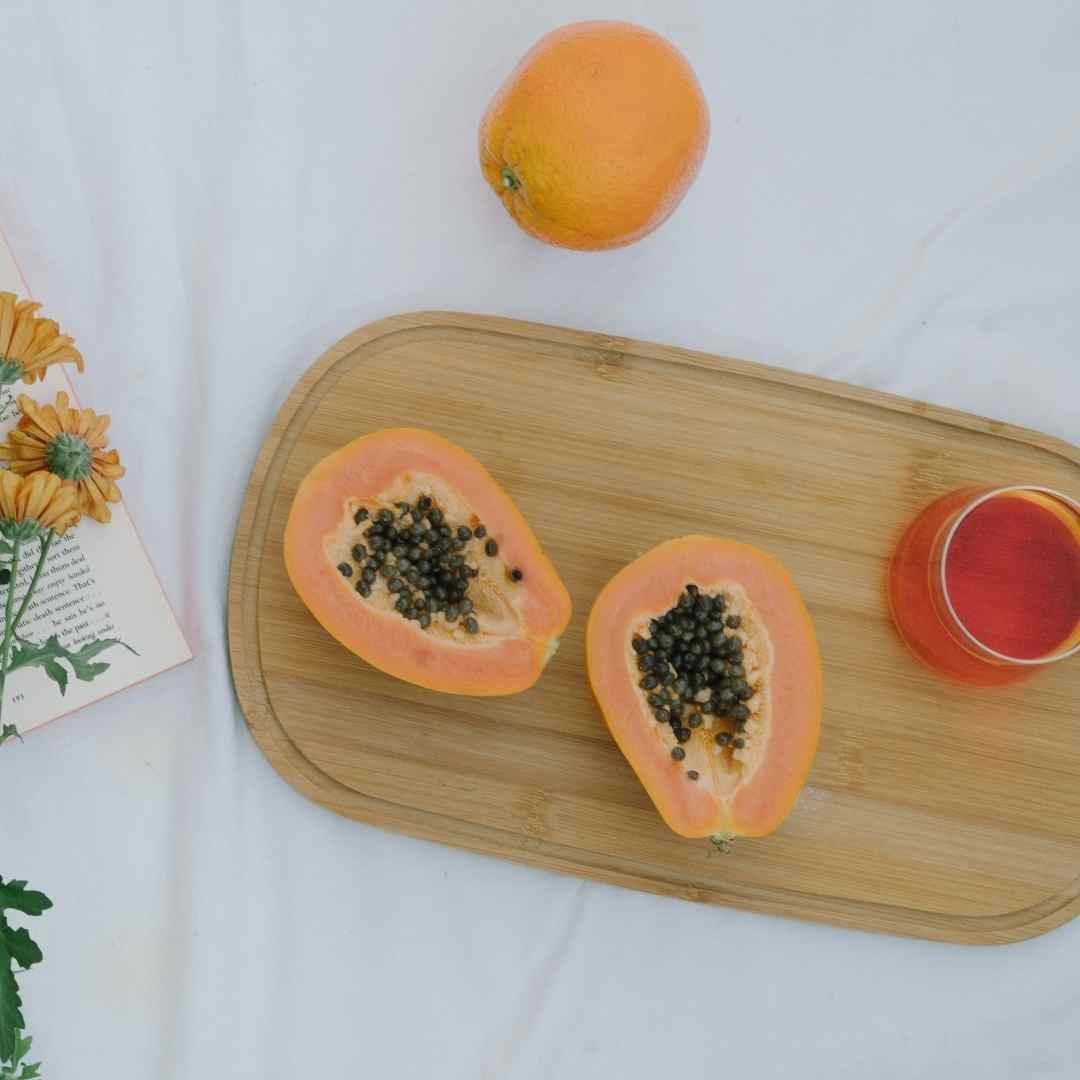 Papaya and a red juice on a timber rectangular board. All placed on a bed with white linen sheets and next to a bunch of yellow flowers and a book that that open